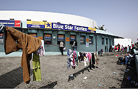 Pictured: Clothes dry next to a ticket office at the port Tuesday 01 March 2016<br /> Re: Migrants at the port of Piraeus, near Athens, Greece