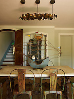 A view over the wrought-iron dining table and rusting chairs that surround it to the simple tiled steps of the staircase leading up to the first floor