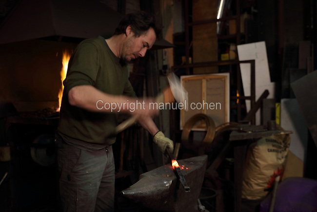 Nicolas Desbons, metalworker and artist, shaping a heated steel rod with a hammer on an anvil by the forge in his Soleil Rouge workshop, photographed in 2017, in Montreuil, a suburb of Paris, France. Desbons works mainly in steel but often in conjunction with other materials such as fibreglass, glass and clay, using both cold metal and forge techniques. He produces both figurative and abstract sculptures as well as furniture and lighting. Picture by Manuel Cohen