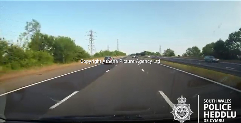 """Pictured: Dashcam video grab showing a blue Mini and a silver Ford Mondeo colliding in the distance on the M4 motorway near Port Talbot, Wales, UK in June 2018.<br /> Re: Two motorists have been convicted of dangerous driving following a road rage incident on the M4 near Port Talbot.<br /> Dash cam footage shows the two men repeatedly undertaking and tailgating each other along the eastbound carriageway in June last year.<br /> The incident eventually led to one of the vehicles – a blue Mini – flipping onto its roof with the driver fortunate to get out of the car unharmed.<br /> Paul Carpenter, aged 44, from Boxhill in Surrey, and Wayne Sebury, 59, from Pontypridd, initially denied any wrongdoing but later pleaded guilty to dangerous driving.<br /> They appeared at Cardiff Crown Court on Thursday 11th April where Carpenter was sentenced to six months in prison and disqualified from driving for 18 months. Sebury was given an 18 month community order and disqualified for 12 months. He must also carry out 150 hours unpaid work.<br /> PC Kathryn Matthews of the South Wales Police Roads Policing Unit said: """"This incident was a classic case of road rage where two motorists have driven dangerously, at high speeds, undertaking, tailgating and flashing their lights.<br /> """"It is sheer luck that nobody was killed or seriously injured and the dash cam footage of the incident sends out a clear message about the consequences of driving in such an irresponsible manner.""""<br /> Expert witness evidence showed that Sebury drove his blue Mini and Carpenter his Ford Mondeo at speeds of upto 101mph shortly prior to the collision."""