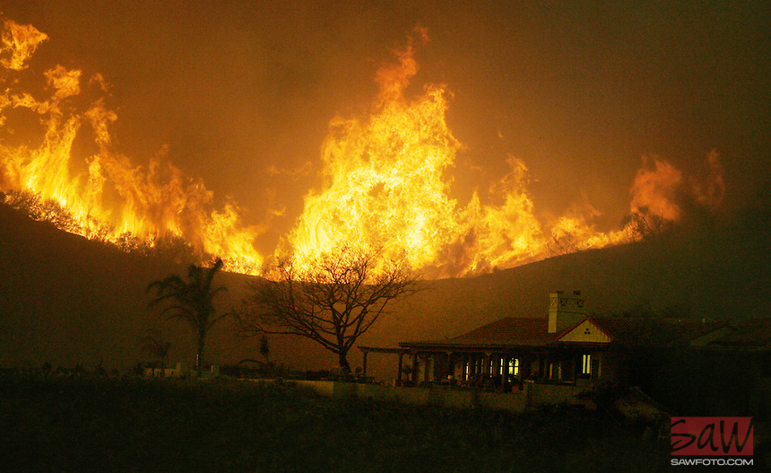 Flames from Santa Barbara's Jesusita Fire threaten a home along spyglass ridge, and darkens the sky above Mission Canyon.