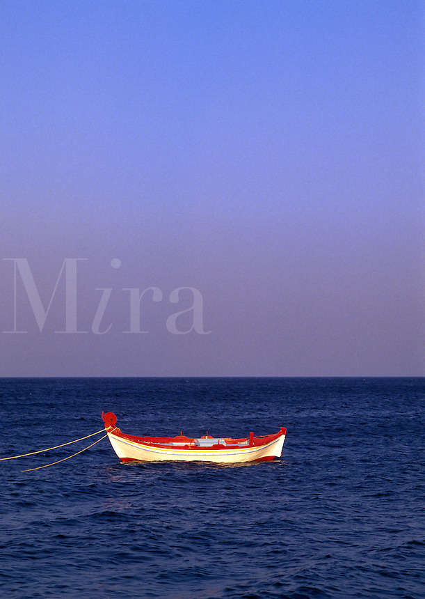 Fishing boat at anchor off beach at Kamari, Santorini, Greece.