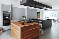 A 'Burnaby St' kitchen by Bulthaup, designed with bold, slab like work surfaces and a hard-wearing stone flagged floor