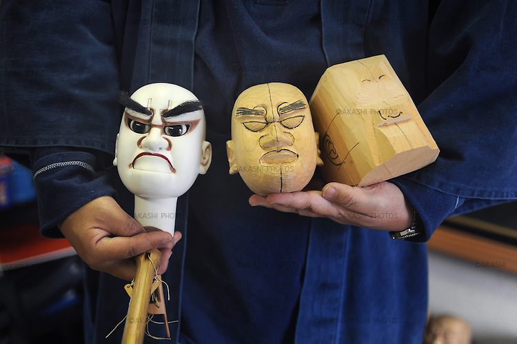 Masayuki Hishida, Bunraku Doll artists, holds the heads of Bunraku ningyo in his studio in Osaka.
