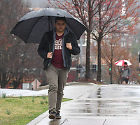 NWA Democrat-Gazette/J.T. WAMPLER  Ricardo Romo of Fayetteville walks to class in the rain Tuesday March 27, 2018 at the University of Arkansas. The National Weather Service is calling for rain the next few days with high temperatures in the 60s. Romo is a chemical engineering graduate student.