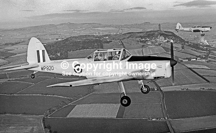 Chipmunks of the University Air Squadron at Queen's University, Belfast, N Ireland, fly over the Co Down Hills, passing Scrabo Tower, during a flight from the then Sydenham Airfield, now Belfast City George Best Airport. The photograph was taken 16th December 1969. Formed 8th January 1941 at Sydenham it was finally disbanded on 31 July 1996. 196912160262d<br />
