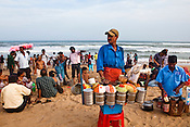 40 year old jhaal-muri (spicy mixture) vendor, Narayan Mehta waits for customers on Puri Beach along the Bay of Bengal in Puri, Orissa, India. A dip in its salty waters is believed to hold great religious significance, as a result these golden sand beaches sees is a never-ending rush of pilgrims and tourists. Photo: Sanjit Das/Panos