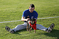 "September 3, 2009:  Pitcher Dave Slovak of the Auburn Doubledays pets ""Haley"" (Batavia Groundskeeper Don Rock's dog) before a game at Dwyer Stadium in Batavia, NY.  Auburn is the Short-Season Class-A affiliate of the Toronto Blue Jays.  Photo By Mike Janes/Four Seam Images"