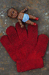Grubby red woollen childs glove lying on rusty metal sheet with small plastic doll of black child
