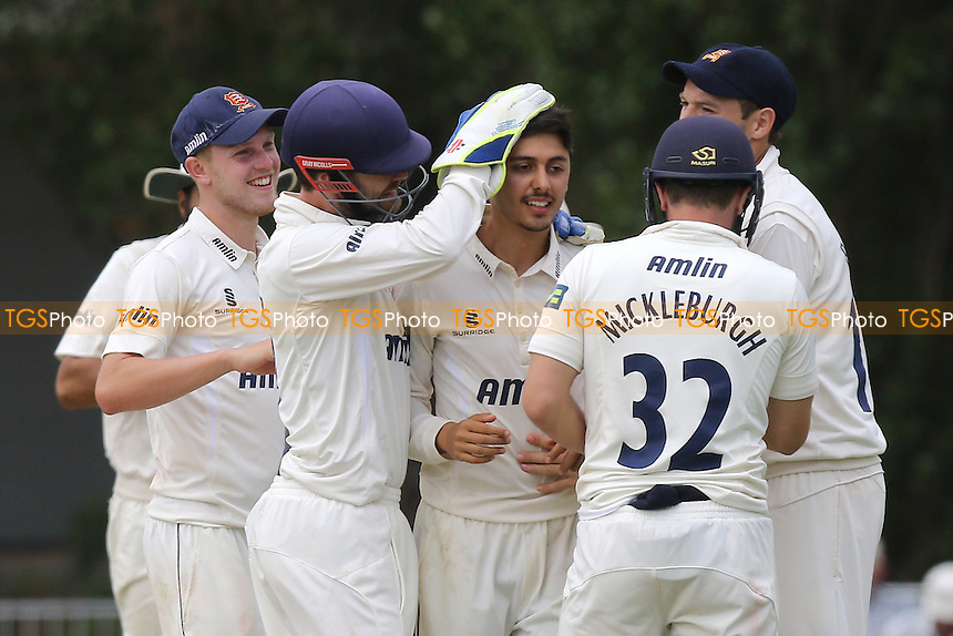 Aron Nijjar of Essex CCC (C) is congratulated by his team mates after taking the wicket of Rory Burns