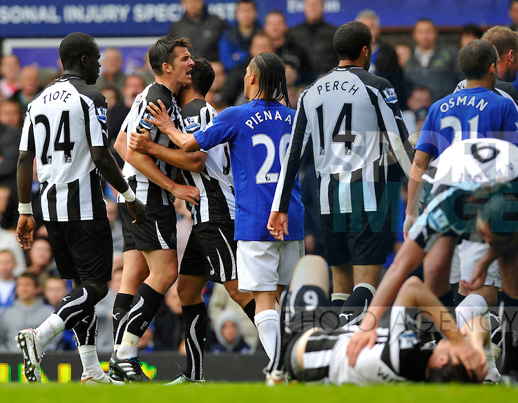 Joey Barton of Newcastle United is held back from a confrontation by Steven Pienaar of Everton