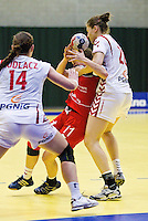 22 MAR 2012 - LOUGHBOROUGH, GBR - Great Britain's Lyn Byl (GBR) (centre, in red and blue) finds her path to goal blocked by Poland's Karolina Kudlacz (POL) (left) and Alina Wojtas (POL) (right) during the women's 2012 European Handball Championships qualification match at Loughborough University in Loughborough, Great Britain (PHOTO (C) 2012 NIGEL FARROW)