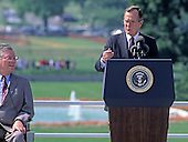 United States President George H. W. Bush makes remarks prior to signing the Americans with Disabilities Act of 1990 into law during a ceremony on the South Lawn of the White House in Washington, D.C. on July 26, 1990. Evan J. Kemp, Jr., Chairman, U.S. Equal Employment Opportunity Commission, looks on from the left.  The act prohibited employer discrimination on the basis of disability. <br /> Credit: Ron Sachs / CNP