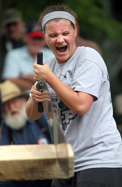 Allison Johnson of Stevens Point, Wisc., celebrates catching a rhythm with her crosscut saw during the wood chopping and sawing contest August 16 at the Iowa State Fair.