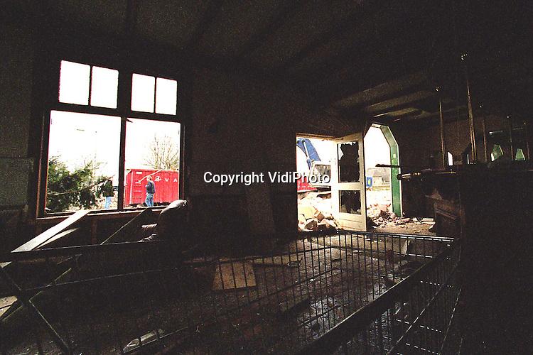 Foto: VidiPhoto..RHEETH - Krakers er uit, slopers er in. Nadat de krakers door de ME uit het voormalige restaurant De Reethse Brug werden gehaald, gingen slopers .woensdag direct aan de slag om het pand tegen de vlakte te werken. De werkzaamheden moesten echter al snel gestaakt worden omdat er asbest werd aangetroffen. Dat wordt de komende dagen eerst verwijderd, voordat het gebouw verder gesloopt wordt.