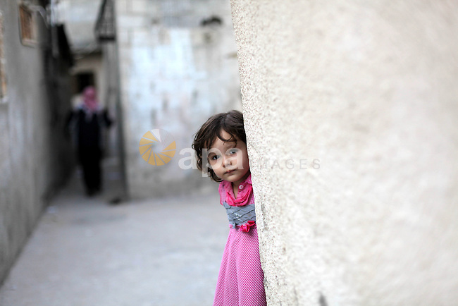 "A Palestinian girl plays outside her home in al-Shati refugees camp, in Gaza city on May 12, 2013, as Palestinians mark the 65 anniversary of the Nakba or ""the catastrophe"" which takes place on May 15, commemorating the expulsion and fleeing of Palestinians from their lands as a result of the 1948 war that led to the creation of the Jewish state. Photo by Ashraf Amra"