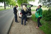 """Am Montag den 13. Mai 2013 wurden drei polnische Saisonarbeiter in Kremmener Ortsteil Staffelde von Einwohnern als vermeintliche Einbrecher verfolgt, geschlagen, gefesselt und verschleppt. Auch nach dem die Frau dem Einbruchhaus den Verfolgern mitteilte, dass die Vertragsarbeiter nicht die Einbrecher seien, liessen die Maenner nicht von ihren Opfern ab. Der Buergermeister der Gemeinde Kremmen und die Stadtverordneten verurteilten den Angriff auf die Polen als rassistische Tat.<br />Am Dienstag den 21. Mai 2013 kamen Mitglieder antirassistischer Gruppen und Fluechtlinge aus Berlin nach Kremmen um mit einer Kundgebung ihren Unmut ueber diese rassistische Tat zum Ausdruck zu bringen.<br />Im Bild: Polizeibeamte kontrollieren Journalisten bei der Einfahrt nach Kremmen, nachdem  ein Schild des Spargelhofes mit Polizeifahrzeugen davor fotografiert wurde. Werder Name noch Dienstnummer wurde genannt. """"Hab ich nich"""" gab der Beamte links zur Antwort.<br />21.5.2013, Kremmen<br />Copyright: Christian-Ditsch.de<br />[Inhaltsveraendernde Manipulation des Fotos nur nach ausdruecklicher Genehmigung des Fotografen. Vereinbarungen ueber Abtretung von Persoenlichkeitsrechten/Model Release der abgebildeten Person/Personen liegen nicht vor. NO MODEL RELEASE! Don't publish without copyright Christian-Ditsch.de, Veroeffentlichung nur mit Fotografennennung, sowie gegen Honorar, MwSt. und Beleg. Konto:, I N G - D i B a, IBAN DE58500105175400192269, BIC INGDDEFFXXX, Kontakt: post@christian-ditsch.de<br />Urhebervermerk wird gemaess Paragraph 13 UHG verlangt.]"""