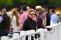 A racegoers watches horses go down to the start during Afternoon Racing at Salisbury Racecourse on 16th May 2019