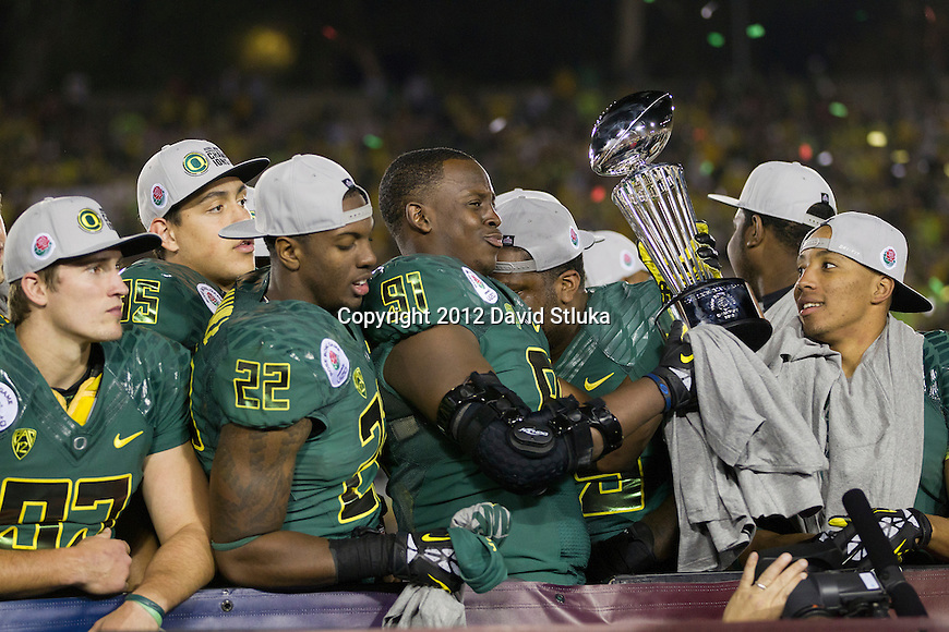 Oregon Ducks defensive lineman Tony Washington (91) holds the 98th Rose Bowl Trophy after beating the Badgers in the 2012 Rose Bowl NCAA football game in Pasadena, California on January 2, 2012. The Ducks won 45-38. (Photo by David Stluka)
