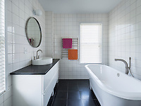 A modern, minimal grey and white tiled bathroom. A round mirror hangs on the wall above a washbasin set on a drawer unit. A free-standing bath stands against one wall. A pink and an orange towel hung over a wall-mounted towel provide a spot of colour.