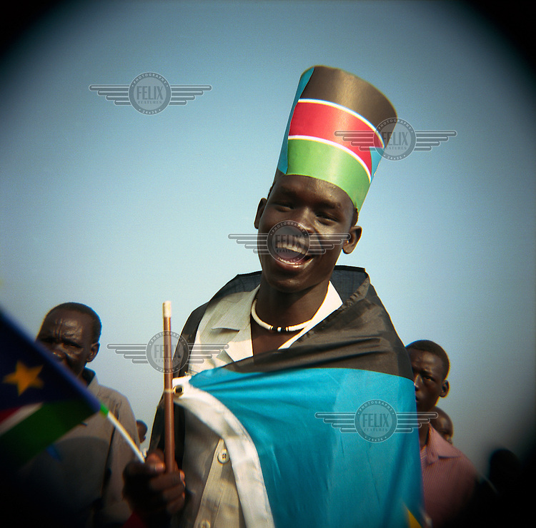A man wrapped with the flag of the newly independent Southern Sudan and a hat of the same flag celebrates near the tomb of John Garang, former rebel leader and head of the Sudan People's Liberation Army (SPLA), during independence celebrations in the new capital Juba. On 9 July 2011 South Sudan became the world's newest nation after seceding from the North.