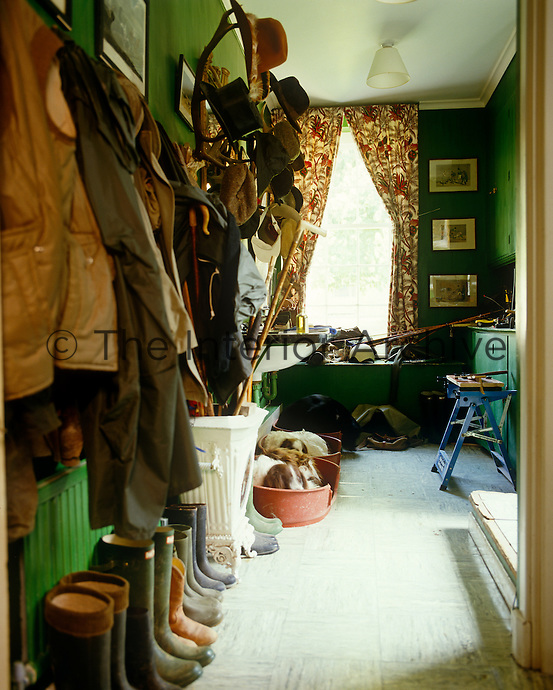 This typical English country cloakroom is filled with outdoor clothing, Wellington boots and sleeping dogs