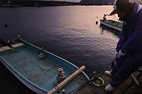 Fisherman Rikio Kikukawa gets into his boat, harvesting wakame at dawn, Awata fishing port, Naruto, Tokushima Prefecture, Japan, February 4, 2012.