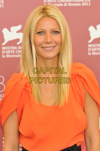 Gwyneth Paltrow.Attending the 'Contagion' photocall during the 68th Venice Film Festival, Venice, Italy, September 3rd, 2011..portrait headshot sleeves smiling  orange .CAP/PL.©Phil Loftus/Capital Pictures.
