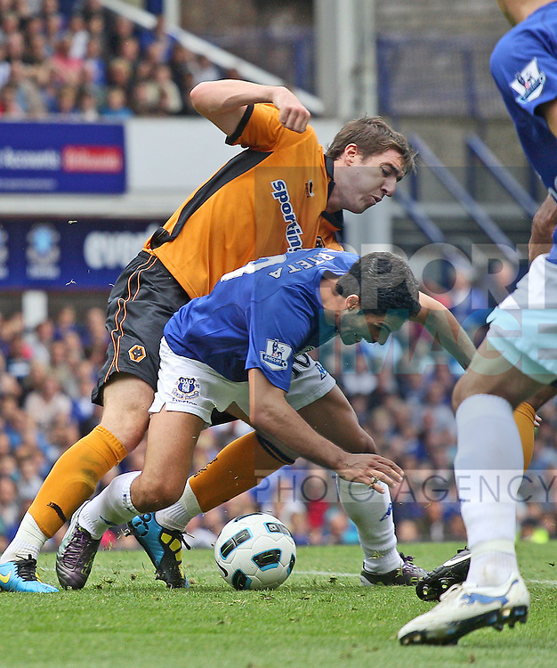 Steven Ward of Wolves (l) fouls Mikel Arteta to concede what should have been a penalty kick, moments before Everton's goal.