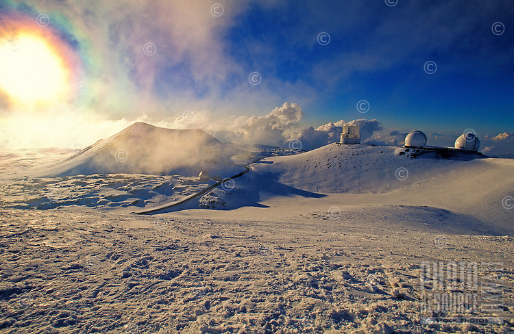 A blazing white sun is reflected off the snow capped summit of Mauna Kea with several observatories in view.