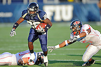 27 November 2010:  FIU running back Darrian Mallary (26) evades Arkansas State linebacker Javon McKinnon (5) in the second quarter as the FIU Golden Panthers defeated the Arkansas State Red Wolves, 31-24, at FIU Stadium in Miami, Florida.