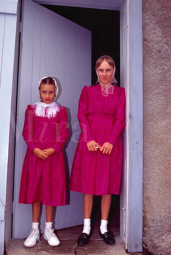 Portait of two Mennonite girls standing in doorway.
