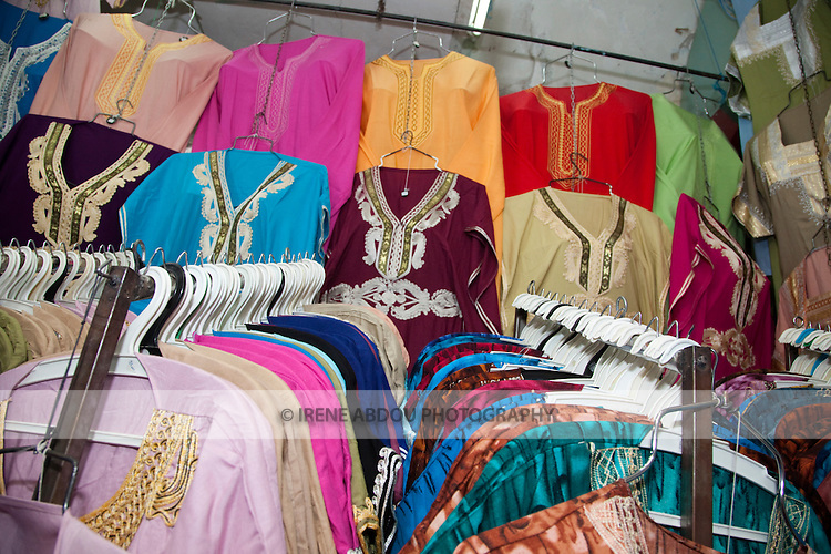 A shop in the Tunis Medina (old city) displays racks of tunics and other clothes in typical Arab style.