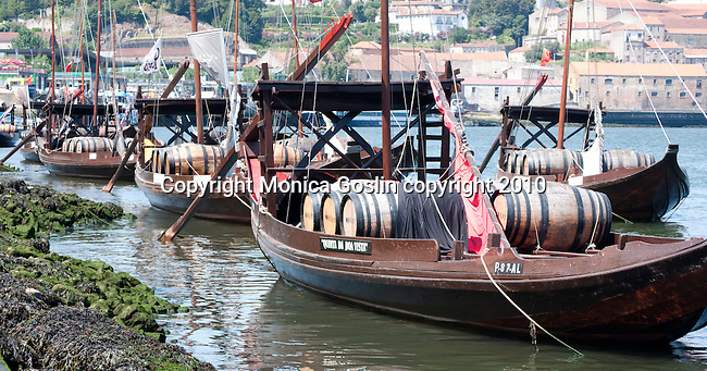 Old port boats used to transport wine barrels sitting on the Douro River in Porto, Portugal.