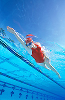 Young woman with red swim suit swimming laps, freestyle, in pool in Coral Springs, Florida.  Underwater view.