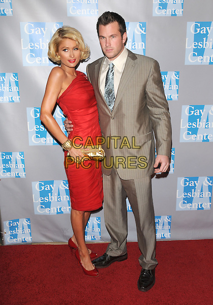 """PARIS HILTON & DOUG REINHARDT .at """"An Evening With Women: Celebrating Art, Music & Equality"""" held at The Beverly Hilton Hotel in Beverly Hills, California, USA, April 24th 2009.                                                                     .full length  red dress gold clutch bag beaded patent shoes one shoulder  bracelet cuff grey gray pinstripe suit  tie couple .CAP/DVS.©Debbie VanStory/RockinExposures/Capital Pictures"""
