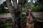 A Cameroonian child who was leading water by the road protects himself of the rain under a tree. In many developing countries children seen in the need to work to have access to the most basic things, help their families, go to school, food or water are just some of them.