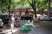 A man eats noodles on a sidewalk in a residential area of western Jiangbei district in Chongqing, China.