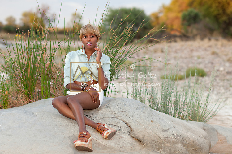 Young fashionable black Namibian woman enjoys nature.