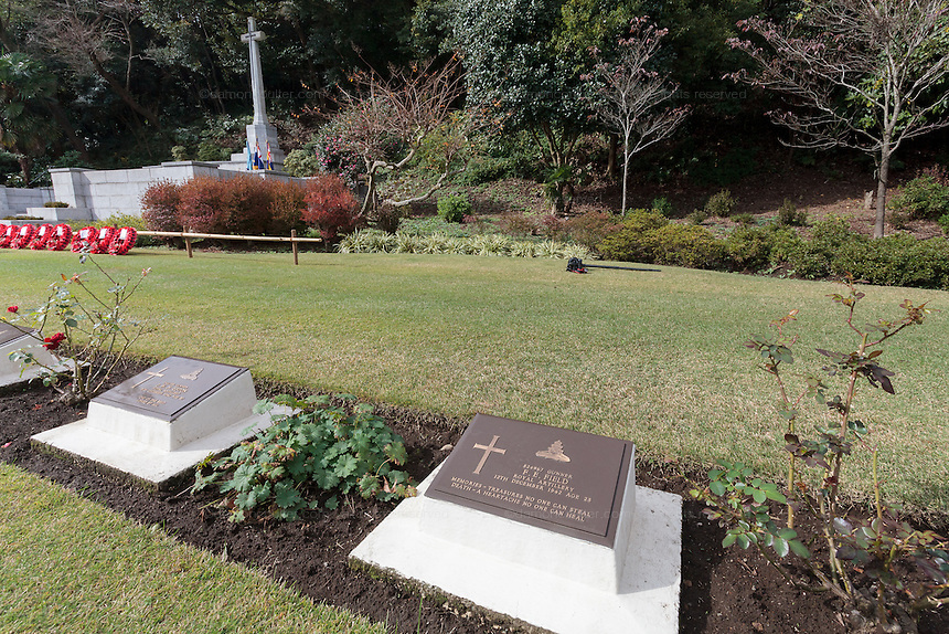 Graves in front of the Cross of Sacrifice  at the Commonwealth War Cemetery in Hodogaya, Yokohama, Japan. Wednesday November 11th 2015
