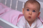 Five month old baby girl in crib looking up with surprised look on face
