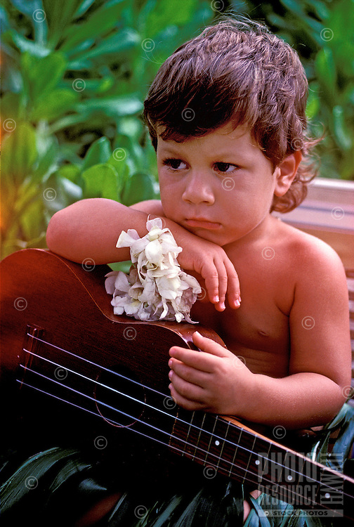 A sweet young local boy wearing a traditional ti leaf skirt and white ginger on his wrist poses with his ukulele outdoors on the Big Island of Hawaii.
