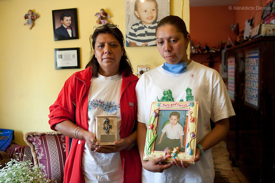 "April 26, 2009 - Mexico City, Mexico - The grandmother (on the left) and the mother (on the right) of Oscar Corona Perez stand with Oscar's ashes and a photograph  in the room of their apartment in Mexico City. Oscar, 5 years old, died yesterday after 8 days of treatment at ""La Raza"" national medical center. The family was told on Friday that the medication and operations that had been done had no effect as Oscar had a new illness with no treatment. The next morning he died at 11:00 AM of pneumonia caused by swine Flu. The death toll has risen to over 80 people in Mexico City, and 929 people have the disease. All dead bodies with the influenza must be cremated. Photo credit: Benedicte Desrus / Sipa Press"