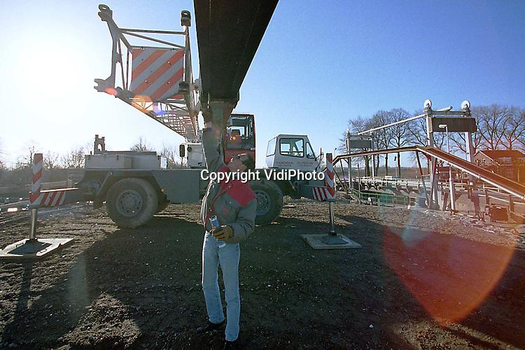 Foto: VidiPhoto..ANDEL - Kraanmachinist Sven Suykerbuyk smeert de telescooparm van zijn mobiele hijskraan in met vet. Dat gebeurt tijdens een rustig moment. De werkzaamheden aan de Wilhelminasluis bij Andel hebben vertraging opgelopen omdat de nieuwe sluisdeuren in eerste instantie werden afgekeurd. Inmiddels zijn ze geplaatst. Daarnaast wordt de beruchte en smalle eenbaansbrug ter plaatse vervangen door een tweebaans klapbrug met parallelweg. Behalve dat het verkeer straks niet meer op elkaar hoeft te wachten, gaat de Wilhelminabrug daardoor ook minder vaak open voor het scheepvaartverkeer op de Afgedamde Maas. Daardoor onstond veel verkeershinder. De doorvaarthoogte wordt 7.80 meter (was 6.60 meter). De bouwkosten bedragen ongeveer 30 miljoen gulden.