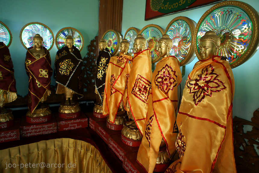 group of Buddha sculptures with electric light halo / nimbus, Sula Paya pagoda complex, center of Yangon, Myanmar, 2011
