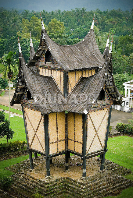 "A traditional ""gonjong"" rice barn decorates the grounds of the Pagaruyung Palace, Batusangkar, West Sumatra. The spired, buffalo horn roof is typical of Minangkabau architecture."