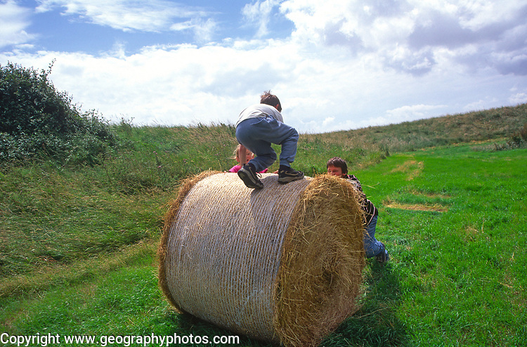 A1X0R2 Children playing on round straw bale in meadow Suffolk Sandlings England