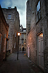 A street scene at dusk with an old man walking away in the distance with street lights in Bath, Somerset, England