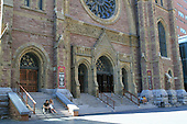 a young couple sitting on the front steps of the St. James United church on Ste-Catherine street west in downtown Montreal on a summer afternoon