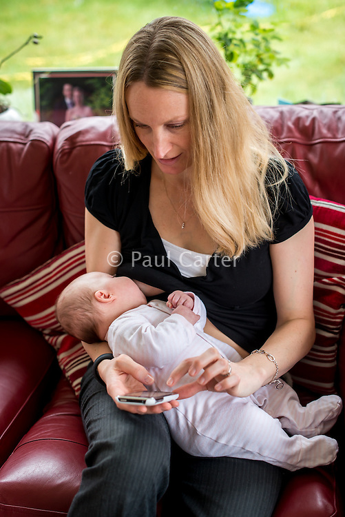 A woman sitting on her living room sofa and texting on her mobile phone while breastfeeding her 2 month old baby.<br /> <br /> Hampshire, England, UK<br /> 10/02/2013